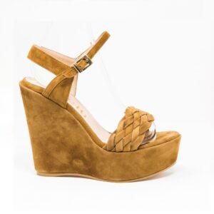 Sandalo in camoscio, cinturino sul collo del piede e fascia intrecciata sul fronte. Altezza zeppa 12,5 cm.